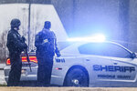 Authorities stand outside a business in Conyers, Ga. on Friday, Dec. 13, 2019. Dart Container Corp. spokeswoman Margo Burrage says a person entered the company's Conyers plant around 7 a.m. with a gun. Burrage says the company has no information about the condition of the person who was shot or the shooter. (John Spink/Atlanta Journal and Constitution via AP)