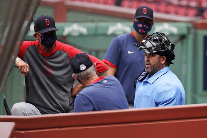 Boston Red Sox coach and homeplate umpire for the day, Jason Varitek, right, talks with manager Ron Roenicke, left foreground, in the dugout during baseball practice at Fenway Park on Thursday, July 9, 2020, in Boston. (AP Photo/Charles Krupa)