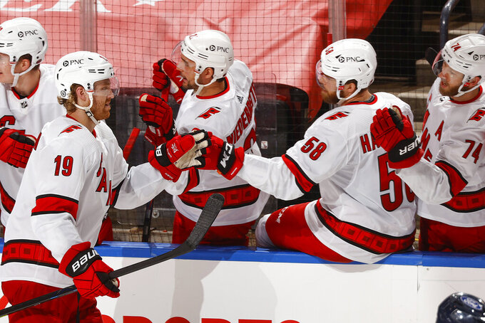 Carolina Hurricanes defenseman Dougie Hamilton (19) is congratulated for his second goal of the night, during the second period of the team's NHL hockey game against the Florida Panthers, Saturday, April 24, 2021, in Sunrise, Fla. (AP Photo/Joel Auerbach)