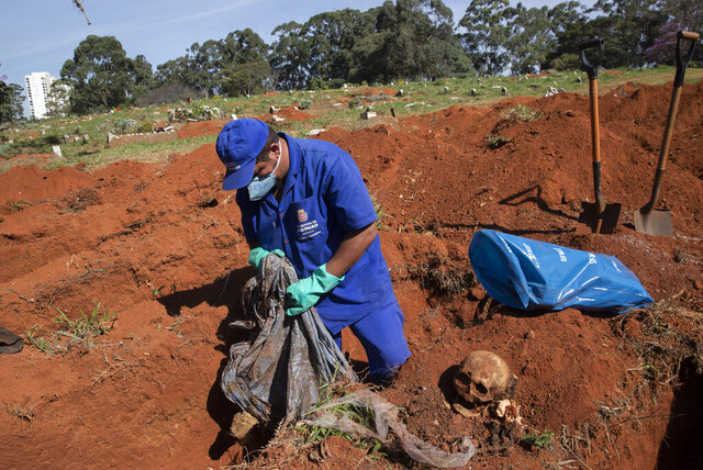 A cemetery worker exhumes the body of a person buried three years ago at the Vila Formosa cemetery, which does not charge families for the gravesites, in Sao Paulo, Brazil, Friday, June 12, 2020. Three years after burials, remains are routinely exhumated and stored in plastic bags to make room for more burials, which have increased amid the new coronavirus. (AP Photo/Andre Penner)