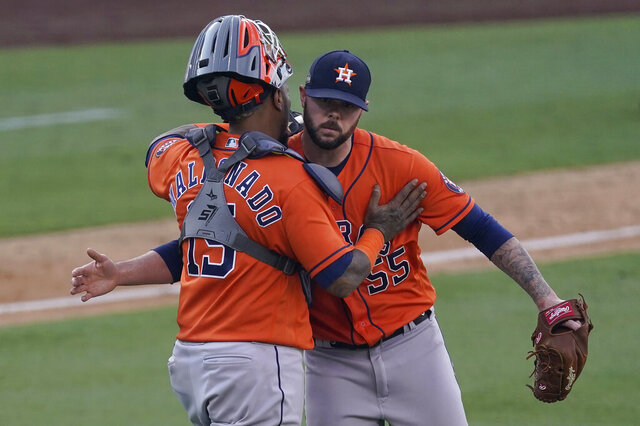 Houston Astros catcher Martin Maldonado, left, hugs relief pitcher Ryan Pressly after they defeated the Oakland Athletics in Game 1 of a baseball American League Division Series in Los Angeles, Monday, Oct. 5, 2020. (AP Photo/Ashley Landis)