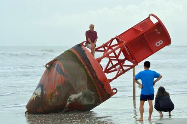 REMOVES REFERENCE TO MOVING THE BUOY ON MONDAY - Beachgoers inspect a navigational marker that washed up on the beach last week in New Smyrna Beach, Fla., Saturday, Dec. 27, 2019. A Coast Guard spokesman said the marker originated in South Carolina. The marker seems to have been on a journey for about two years.  (Casmira Harrison/The Daytona Beach News-Journal via AP)