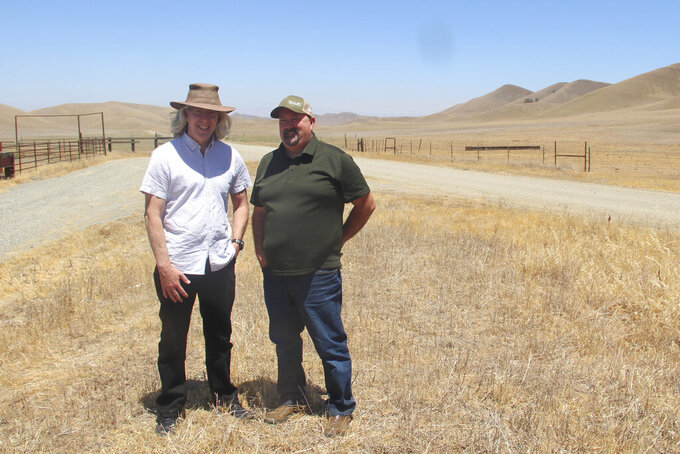 Jerry Brown, left, and Kevin Spesert stand at what would be the bottom of the Sites Reservoir in Sites, Calif., on Friday, July 23, 2021. Brown is the executive director of the Sites Project Authority and Spesert is the authority's public affairs and real estate manager. The project would be used to store water during wet years for use during droughts. The reservoir would be large enough to supply water for 1.5 million households each for one year. (AP Photo/Adam Beam)