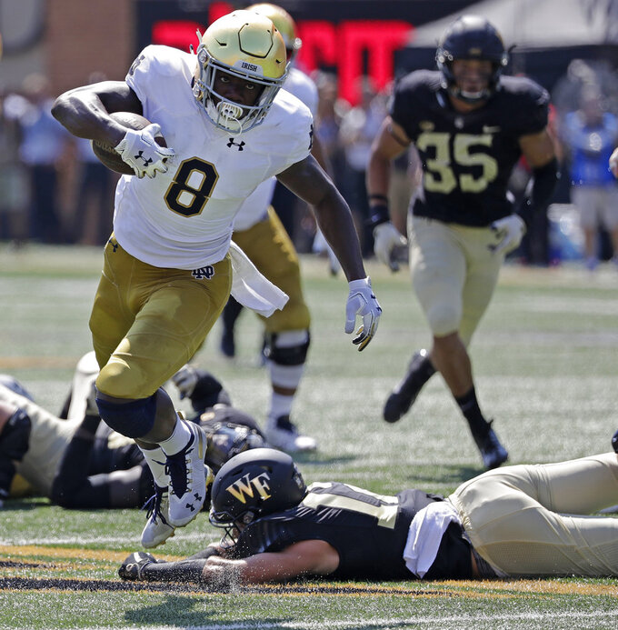 Notre Dame's Jafar Armstrong (8) runs past Wake Forest's Luke Masterson (12) in the first half of an NCAA college football game in Winston-Salem, N.C., Saturday, Sept. 22, 2018. (AP Photo/Chuck Burton)
