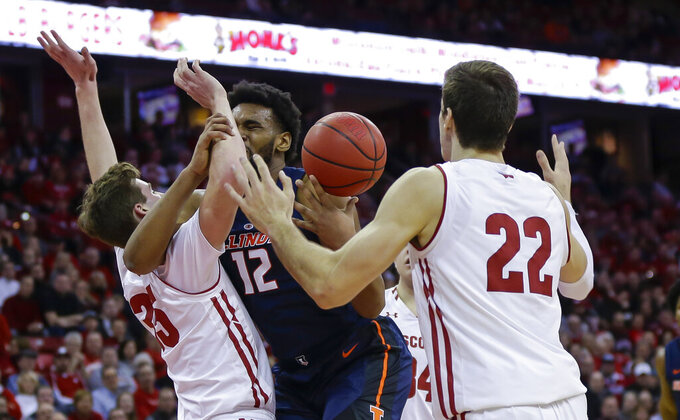 Illinois' Adonis De La Rosa, center, looses control of the ball against Wisconsin's Nate Reuvers, left, and Ethan Happ, right,  during the first half of an NCAA college basketball game Monday, Feb. 18, 2019, in Madison, Wis. (AP Photo/Andy Manis)