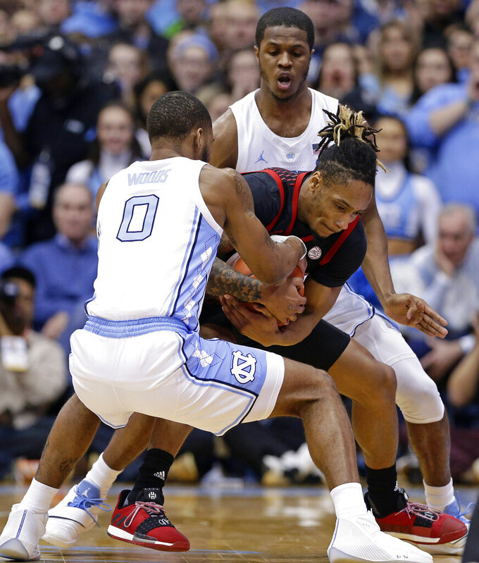 North Carolina's Seventh Woods, left, and Kenny Williams, right, guard Louisville's Khwan Fore, center, during the first half of an NCAA college basketball game in Chapel Hill, N.C., Saturday, Jan. 12, 2019. (AP Photo/Gerry Broome)
