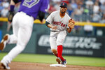 Boston Red Sox shortstop Xander Bogaerts, back, fields the throw from first baseman Mitch Moreland to force out Colorado Rockies' Trevor Story at second base on the front end of a double play hit into by Charlie Blackmon in the first inning of a baseball game Wednesday, Aug. 28, 2019, in Denver. (AP Photo/David Zalubowski)