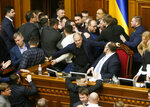 Ukrainian lawmakers scuffle around the rostrum during a parliament session in Kyiv, Ukraine, Thursday, Feb. 6, 2020. The Ukrainian parliament is considering changes to laws restricting the sale of farmland. (AP Photo/Efrem Lukatsky)