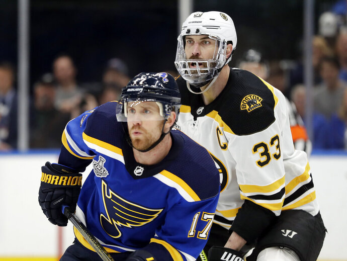 Boston Bruins defenseman Zdeno Chara (33), of Slovakia, wears a mask to protect his injured jaw as he and St. Louis Blues left wing Jaden Schwartz (17) play during the second period of Game 6 of the NHL hockey Stanley Cup Final Sunday, June 9, 2019, in St. Louis. (AP Photo/Jeff Roberson)