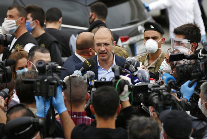 In this Sunday, April 5, 2020, Lebanese Health Minister Hamad Hassan, center, ignoring social distancing rules and not wearing mask, speaks with journalists during the arrival of Lebanese passengers who were stuck in Saudi Arabia and other countries because of the coronavirus outbreak, outside Rafik Hariri Airport, in Beirut. From the U.S. president to the British prime minister's top aide and far beyond, leading officials around the world are refusing to wear masks or breaking confinement rules meant to protect their populations from the coronavirus and slow the pandemic. While some are punished when they're caught, or publicly repent, others shrug off the violations as if the rules don't apply to them. (AP Photo/Hussein Malla)