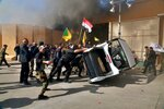 FILE - In this Dec 31, 2019  file photo, pro-Iranian militiamen and their supporters damage property inside the U.S. embassy compound, in Baghdad, Iraq. The Trump administration has signaled it could close its diplomatic mission in Baghdad if measures are not taken to control rogue armed elements responsible for a recent spate of attacks against U.S. and other interests in the country, Iraqi and U.S. officials said Monday, Sept. 28, 2020. (AP Photo/Khalid Mohammed, File)