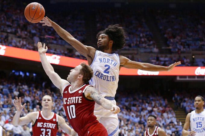 North Carolina's Coby White (2) blocks North Carolina State's Braxton Beverly (10) during the second half of an NCAA college basketball game in Chapel Hill, N.C., Tuesday, Feb. 5, 2019. North Carolina won 113-96. (AP Photo/Gerry Broome)