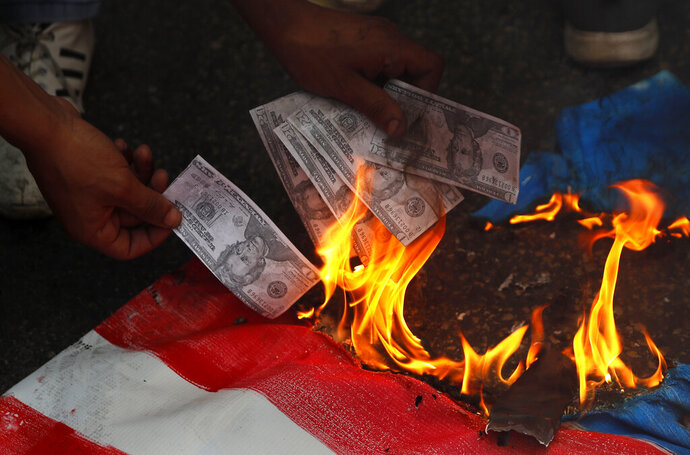 A supporter of a communist group burns representation of U.S. currency, during a protest against U.S. interference in Lebanon's affairs, near the U.S. embassy, in Aukar northeast of Beirut, Lebanon, Friday, July 10, 2020. (AP Photo/Hussein Malla)