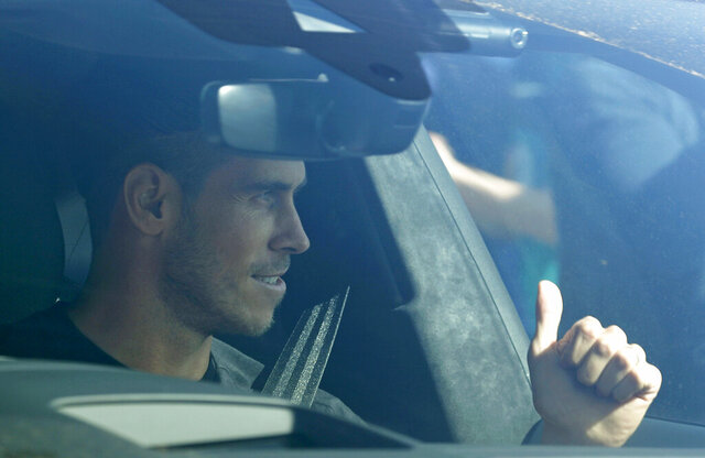 Soccer player Gareth Bale gestures to fans as he arrives at the training ground of Tottenham Hotspur in London, Friday Sept. 18, 2020. Real Madrid winger Gareth Bale is in London to complete his return to Tottenham. Bale left Tottenham for Madrid in 2013 for 100 million euros. (AP Photo/Frank Augstein)