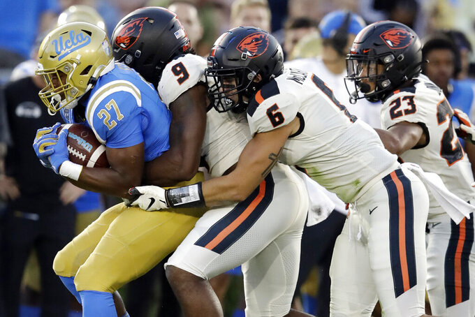 FILE - In this Oct. 5, 2019, file photo, UCLA running back Joshua Kelley, left, is tackled by Oregon State linebackers Hamilcar Rashed Jr. (9) and John McCartan (6) during the first half of an NCAA college football game in Pasadena, Calif. While the offense is still coming together with presumed starting quarterback Tristan Gebbia, it's Oregon State's defense that should worry opponents. (AP Photo/Marcio Jose Sanchez, File)