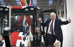 Britain's Prime Minister Boris Johnson signals to the media during an election campaign visit to the JCB manufacturing facility in Uttoxeter, England, Tuesday Dec. 10, 2019.  The Conservative Party are campaigning for their Brexit split with Europe ahead of the UK's General Election on Dec. 12.(Stefan Rousseau/PA via AP)