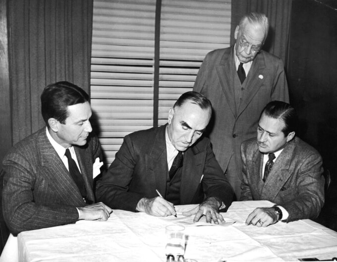 "FILE - In this Nov. 14, 1945, file photo, Eddie Rickenbacker, center, signs papers selling the Indianapolis Motor Speedway to Anton ""Tony"" Hulman Jr., left, as Wilbur Shaw, right, and T.E. Myers looks on in Indianapolis. Indianapolis Motor Speedway and the IndyCar Series have been sold to Penske Entertainment Corp. in a stunning announcement that relinquishes control of the iconic speedway from the Hulman family after 74 years. (AP Photo/File)"