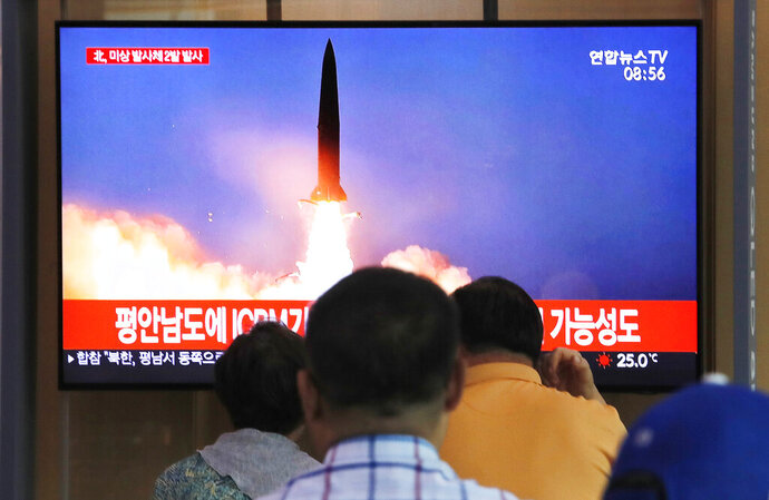People watch a TV showing a file image of a North Korea's missile launch during a news program at the Seoul Railway Station in Seoul, South Korea, Tuesday, Sept. 10, 2019. North Korea launched at least two unidentified projectiles toward the sea on Tuesday, South Korea's military said, hours after the North offered to resume nuclear diplomacy with the United States but warned its dealings with Washington may end without new U.S. proposals. The sign reads