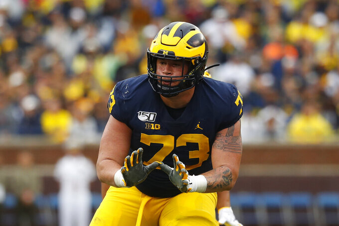 FILE - Michigan offensive lineman Jalen Mayfield (73) blocks against Rutgers in the first half of an NCAA college football game in Ann Arbor, Mich., Saturday, Sept. 28, 2019. Mayfield is entering the NFL draft. The junior announced his plans Tuesday, Aug. 18, 2020 on Twitter. Mayfield chose to leave the Wolverines one week after the Big Ten postponed its fall football season because of the coronavirus pandemic. (AP Photo/Paul Sancya)