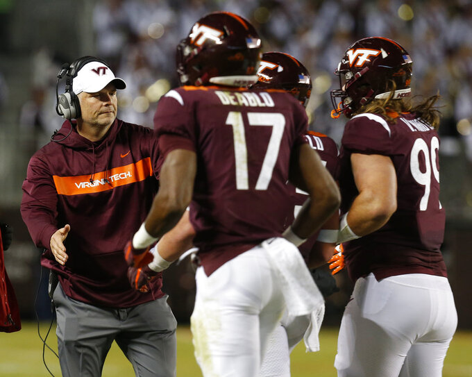 Virginia Tech head coach Justin Fuentes, left, greets his team during the first half of an NCAA college football game against Georgia Tech in Blacksburg, Va., Thursday, Oct. 25, 2018. (AP Photo/Steve Helber)