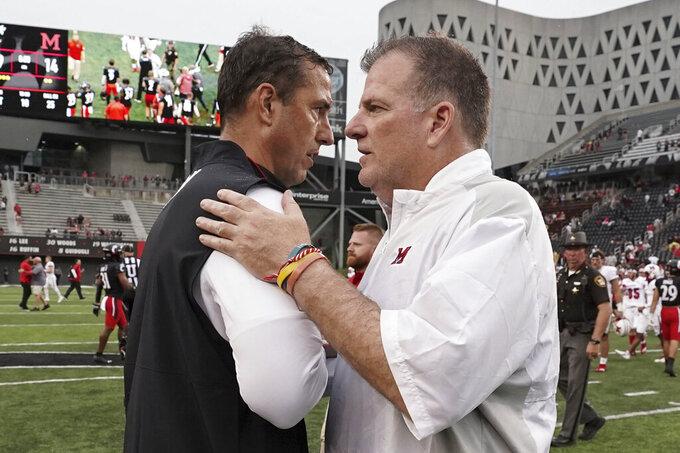 Cincinnati head coach Luke Fickell, left, shakes hands with Miami (Ohio) head coach Chuck Martin, right, at the completion of an NCAA college football game Saturday, Sept. 4, 2021, in Cincinnati. (AP Photo/Jeff Dean)