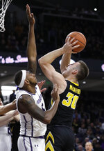 Iowa guard Connor McCaffery, right, shoots against Northwestern center Dererk Pardon during the first half of an NCAA college basketball game Wednesday, Jan. 9, 2019, in Evanston, Ill. (AP Photo/Nam Y. Huh)