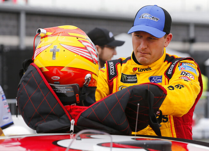 Michael McDowell, unpacks his helmet prior to qualifying for Saturday's NASCAR Cup auto race at Richmond International Raceway in Richmond, Va., Friday, April 12, 2019. (AP Photo/Steve Helber)