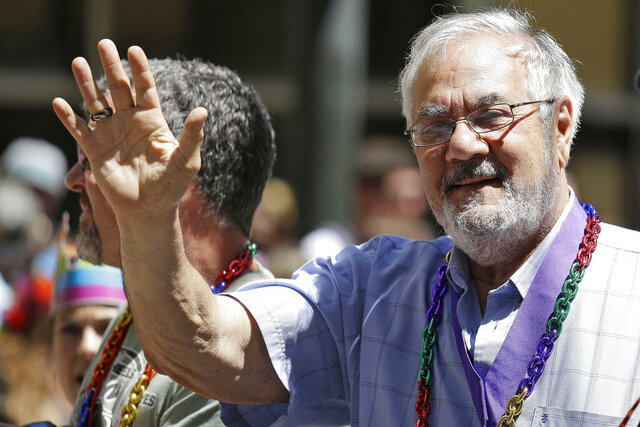 FILE - In this June 29, 2014, file photo, former Massachusetts congressman Barney Frank, right, waves while riding with his husband James Ready, left, during the 44th annual San Francisco Gay Pride parade in San Francisco. Frank and Ready filed a lawsuit Wednesday, Dec. 2, 2020, against a construction contractor who they said abandoned the building of their home in Maine in May after only completing part of the agreed upon work. (AP Photo/Eric Risberg, File)