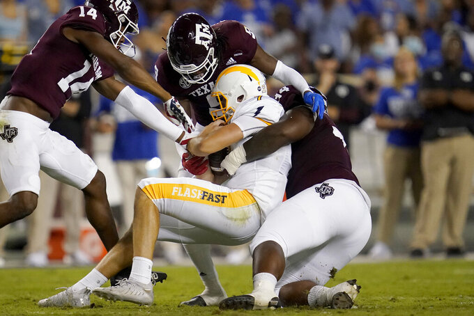 Kent State quarterback Dustin Crum (7) is tackled by Texas A&M defensive lineman Isaiah Raikes (34) and defensive back Leon O'Neal Jr. (9) after a short run during the first half of an NCAA college football game on Saturday, Sept. 4, 2021, in College Station, Texas. (AP Photo/Sam Craft)