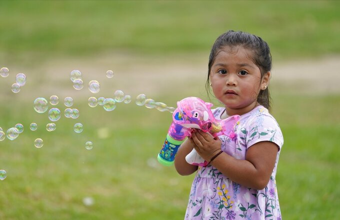 Zoe Olea, 2, plays with bubbles at Echo Park in Los Angeles Monday, Aug. 17, 2020. A heat wave brought triple-digit temperatures and raised wildfire danger and fears of coronavirus spread, a significant concern in a state with more than 621,000 confirmed cases. Public health officers urged people to follow masks and social distancing orders if they head outdoors. (AP Photo/Damian Dovarganes)