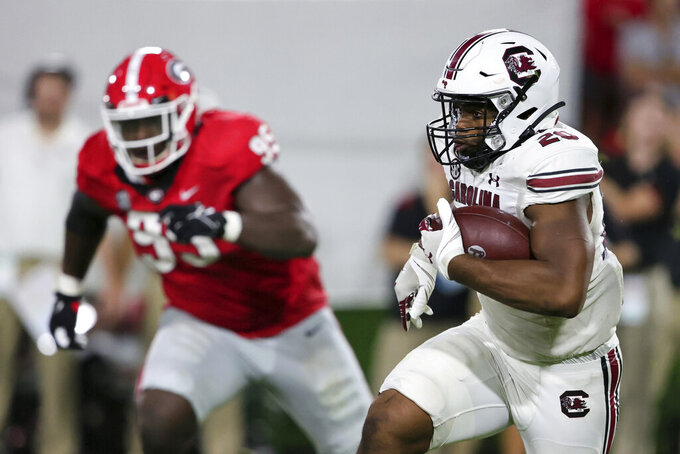South Carolina running back Kevin Harris (20) carries the ball against Georgia during the first half of an NCAA college football game Saturday, Sept. 18, 2021, in Athens, Ga. (AP Photo/Butch Dill)