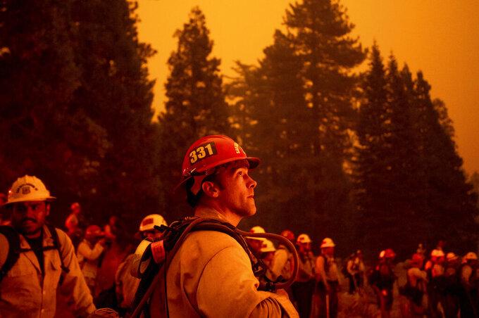 Capt. Adam Tinker monitors a firing operation, where crews burn vegetation to create a control line, while battling the Caldor Fire in Eldorado National Forest, Calif., on Thursday, Aug. 26, 2021. (AP Photo/Noah Berger)