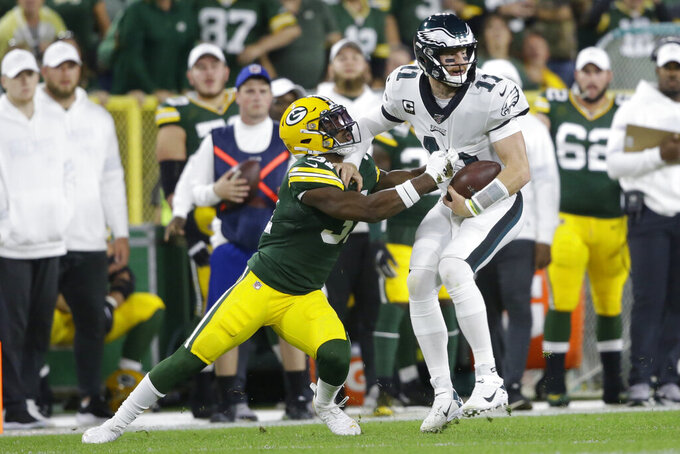 Philadelphia Eagles quarterback Carson Wentz is hit by Green Bay Packers strong safety Adrian Amos on a carry during the first half of an NFL football game Thursday, Sept. 26, 2019, in Green Bay, Wis. (AP Photo/Jeffrey Phelps)