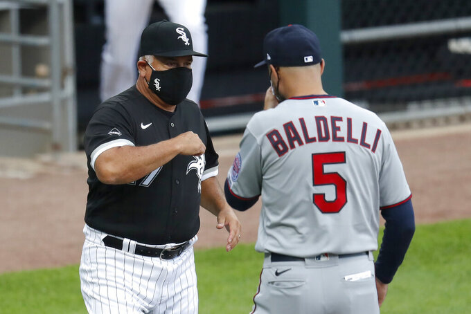 Chicago White Sox manager Ricky Renteria, left, bumps elbows with Minnesota Twins' manager Rocco Baldelli, before the White Sox's home opener baseball game Friday, July 24, 2020, in Chicago. (AP Photo/Charles Rex Arbogast)