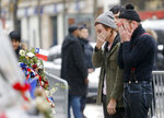 FILE - In this Dec.8, 2015 file photo, members of the band Eagles of Death Metal, Jesse Hughes, right, and Julian Dorio pay their respects to 89 victims who died in a Nov. 13 attack, at the Bataclan concert hall in Paris. France is putting on trial 20 men accused in the Nov. 13, 2015, Islamic State terror attacks on Paris that left 130 people dead and hundreds injured. Nine gunmen and suicide bombers struck within minutes of each other at the national soccer stadium, the Bataclan concert hall and restaurants and cafes. The lone survivor of the terror cell from that night is among those being tried for the deadliest attack in France since World War II. (AP Photo/Jacques Brinon, File)