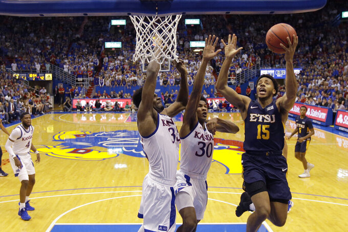 East Tennessee State guard Isaiah Tisdale (15) puts up a shot under pressure from Kansas center Udoka Azubuike, left, and guard Ochai Agbaji (30) during the second half of an NCAA college basketball game Tuesday, Nov. 19, 2019, in Lawrence, Kan. Kansas won 75-63. (AP Photo/Charlie Riedel)
