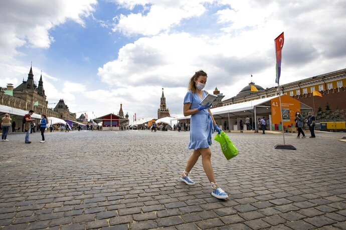 A woman read a book as she walks at an outdoor book market in the Red Square with GUM, State Department store at left, St. Basil's Cathedral, center and the Kremlin Wall, right, in Moscow, Russia, Saturday, June 6, 2020. Muscovites clad in face masks and gloves ventured into Red Square for an outdoor book market, a small sign of the Russian capital's gradual efforts to open up amid coronavirus concerns. (AP Photo/Alexander Zemlianichenko)