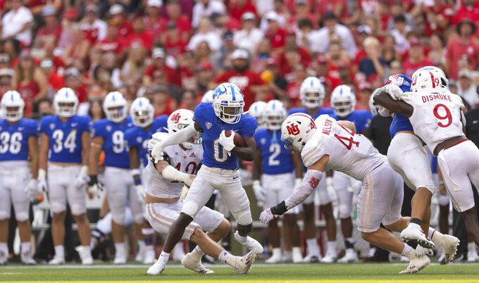 Buffalo's Khamran Laborn (0) carries the ball between Nebraska's Nick Henrich (42) and Garrett Nelson (44) during the second half of an NCAA college football game Saturday, Sept. 11, 2021, at Memorial Stadium in Lincoln, Neb. (AP Photo/Rebecca S. Gratz)