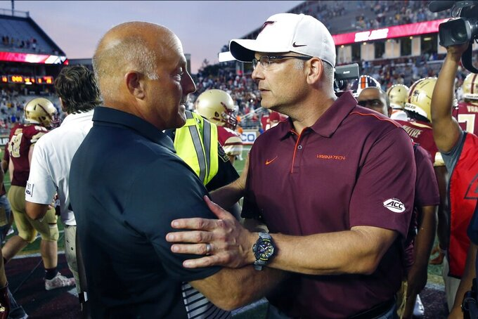 Boston College head coach Steve Addazio, left, and Virginia Tech head coach Justin Fuente shake hands following an NCAA college football game in Boston, Saturday, Aug. 31, 2019. (AP Photo/Michael Dwyer)