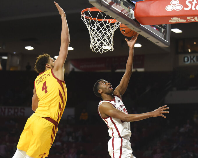 Oklahoma guard Jamal Bieniemy (24) releases a shot next to Iowa State forward George Conditt IV (4) during the second half of an NCAA college basketball game in Norman, Okla., Wednesday, Feb. 12, 2020. (AP Photo/Kyle Phillips)