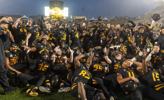 The Missouri football team poses with the Battle Line Rivalry trophy after a 38-0 win over Arkansas inan NCAA college football game Friday, Nov. 23, 2018, in Columbia, Mo. (AP Photo/L.G. Patterson)