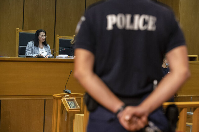 Presiding judge Maria Lepenioti reads the sentences during the Golden Dawn trial, in Athens, Wednesday, Oct. 14, 2020. The court has sentenced the leadership of Greece's extreme-right Golden Dawn party to 13 years in prison, imposing the near-maximum penalty for running a criminal organization blamed for numerous violent hate crimes. The landmark ruling follows a five-year trial of dozens of top officials, members, and supporters of Golden Dawn, an organization founded as a Neo-Nazi group in the 1980s, that rose to become Greece's third-largest political during a major financial crisis in the previous decade.(AP Photo/Petros Giannakouris)