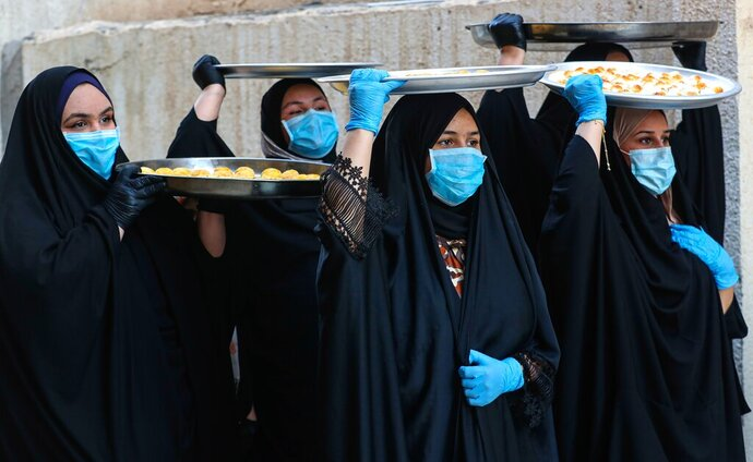 Iraqi women wearing face masks for protection against the spread of the new coronavirus, carry cookies for the upcoming Muslim Eid al-Fitr celebrations that mark the end of the Muslim holy fasting month of Ramadan, in Basra, Iraq, Friday, May 22, 2020. (AP Photo/Nabil al-Jurani)