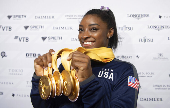 Simone Biles of the United States shows her five gold medals she won at the Gymnastics World Championships in Stuttgart, Germany, Sunday, Oct. 13, 2019. (Marijan Murat/dpa via AP)