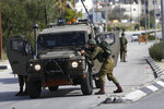 Israeli soldiers conduct a search for suspects of a shooting attack yesterday in the West Bank City of Ramallah, Monday, Dec. 10, 2018. Israeli officials say seven people have been wounded, one critically, in a shooting by a suspected Palestinian assailant outside a Jewish settlement of Ofra in the West Bank. (AP Photo/Majdi Mohammed)