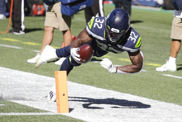 Seattle Seahawks running back Chris Carson (32) dives near the end zone during the first half of an NFL football game against the Dallas Cowboys, Sunday, Sept. 27, 2020, in Seattle. The Seahawks won 38-31. (AP Photo/John Froschauer)