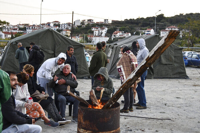 Locals sit around a fire near tents after an earthquake, at the village of Kokkari on the eastern Aegean island of Samos, Greece, Saturday, Oct. 31, 2020. A strong earthquake struck in the Aegean Sea between the Turkish coast and the Greek island of Samos, forcing people to live outside in fear of aftershocks. (AP Photo/Michael Svarnias)