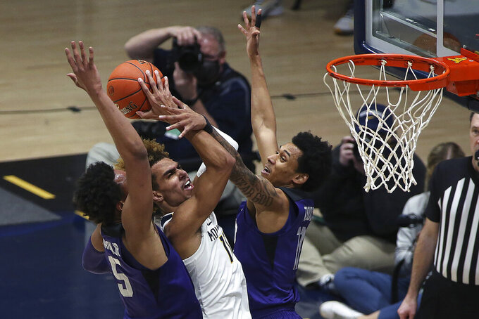 West Virginia forward Emmitt Matthews Jr. (11) shoots while defended by Texas Christian forward Chuck O'Bannon Jr. (5) and guard Taryn Todd (11) during the second half of an NCAA college basketball game Thursday, March 4, 2021, in Morgantown, W.Va. (AP Photo/Kathleen Batten)