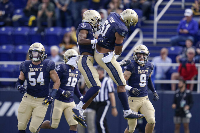 Navy cornerback Jamal Glenn, center left, celebrates with linebacker Nicholas Straw after Glenn intercepted a pass from Cincinnati quarterback Desmond Ridder, not visible, during the first half of an NCAA college football game, Saturday, Oct. 23, 2021, in Annapolis, Md. (AP Photo/Julio Cortez)