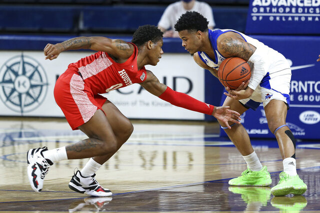Tulsa's Elijah Joiner is guarded by Houston's Marcus Sasser during the first half of an NCAA college basketball game in Tulsa, Okla., Tuesday, Dec. 29, 2020. (AP Photo/Dave Crenshaw)
